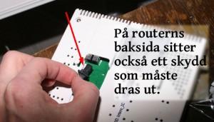 Drag ur gummiproppen ur routern, enligt bild.